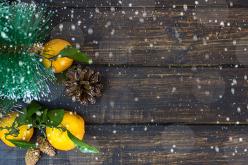 Mandarin fruits, Christmas tree branches and cones on a rustic background in the snow. Christmas holidays