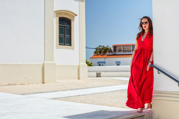 Saxy caucasus lady in red dress behind the wall in Portugal