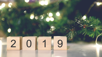 Fototapete - Wooden cubes with Happy new year 2019 with light bokeh background with copy space for text.