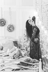 Christmas, winter holidays concept. Beautiful young woman in vintage dress posing in apartments decorated for Christmas. Beauty, fashion.