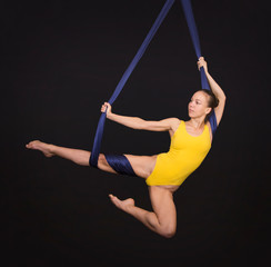 Young, smiling girl doing exercises on aerial silk . Studio shooting on a dark background.