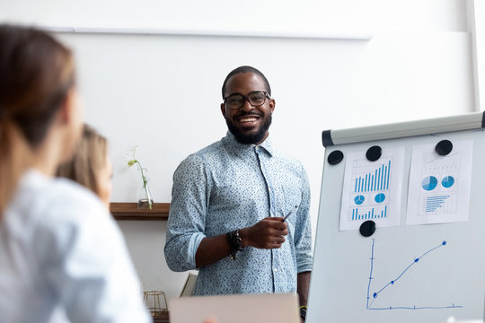 Black coach presents for company members financial report standing near whiteboard where shown sales statistics in graphs. Confident company owner teach interns acquaints with nuances of the market
