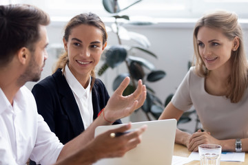 During business meeting in office conference room diverse millennial entrepreneurs businesswomen and businessman share experiences, discuss new ideas and plan joint mutually beneficial cooperation