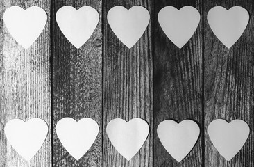 frame of paper hearts on wooden retro grunge background with copy space, top view flat lay, black and white photo