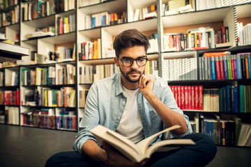 Cute smiling hipster boy sitting on a library floor and looking through some books.