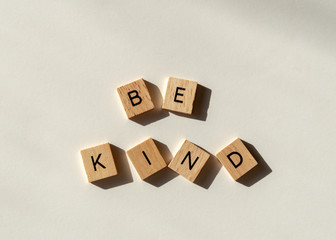 Be kind spelled in wooden letter tiles flat lay