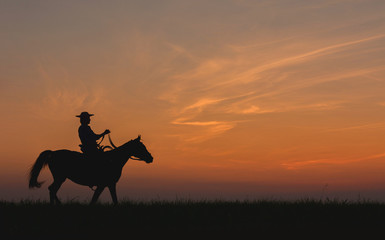 Cowboy in hat riding horse on colorful cloudy sky at sunset. Silhouette of  cowboy travel in wild west mountain like western film background Wall mural