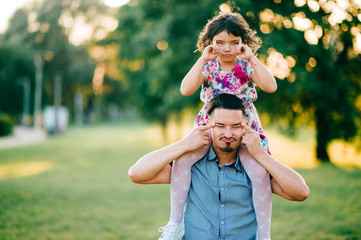 Lifestyle sunset portrait of unusual couple of dad with daughter on shoulders making funny expressive faces. Happy family playing at summer nature outdoor. Fatherhood and childhood. Dad loves his girl