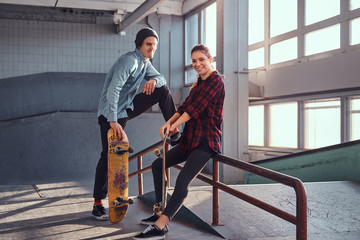 Cheerful youth couple with skateboards wearing casual clothes posing next to a grind rail in skatepark indoors.
