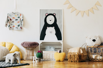 Stylish scandinavian newborn baby room with colorful toys, teddy bears, pillows and blankets. Modern interior with mock up photo frame.