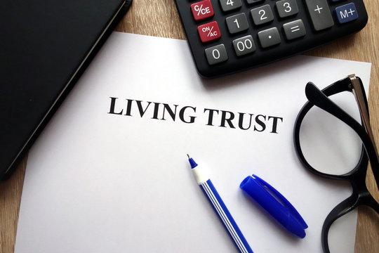 Living trust document, pen, glasses and calculator on   desk