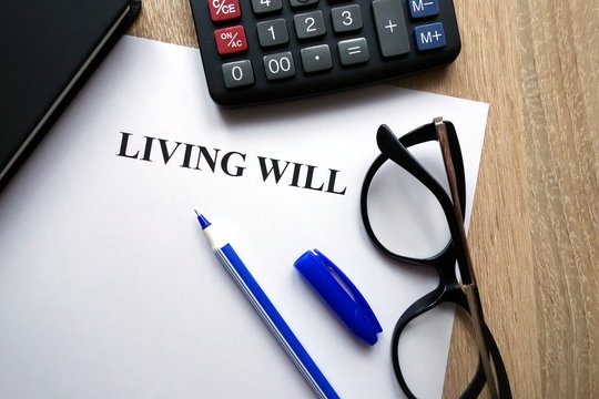 Living will document, pen, glasses and calculator on desk