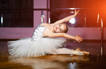 Charming little girl ballet dancer in white tutu performing ballet poses on the floor in the studio background. A small sweet ballerina sitting on wooden floor in a dance studio.