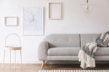 Minimalistic scandinavian interior with design sofa, coffee table, cozy blanket, poster map and mock up photo frames. White background walls and modern triangle lamp.