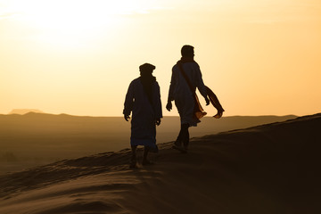 Silhouette of Berber and camel at bloody red sunset, Merzouga in Morocco, Sahara Desert, North Africa.
