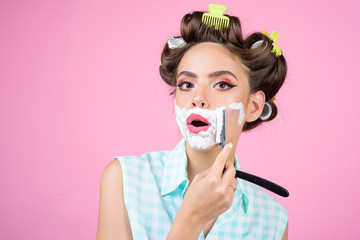 pinup girl with fashion hair. pin up woman with makeup. morning grooming and skincare. retro woman shaving with foam and razor blade. pretty girl in vintage style, copy space. Beauty and fashion