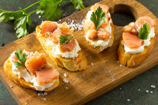Antipasti snacks for Wine. Brushetta with Soft Cheese and Salmon on a rustic wooden board on a stone table.