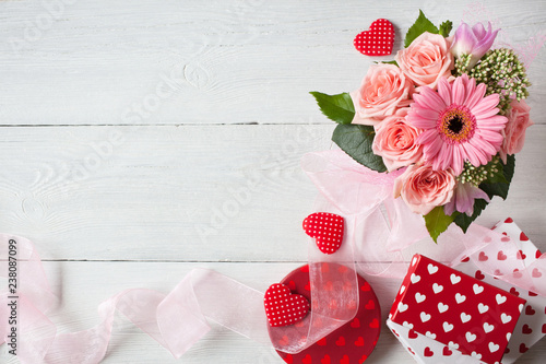 Background with a bouquet of pink roses,  gerbera, ribbon, hearts and gift boxes