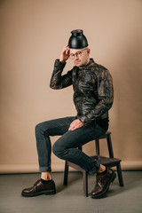 Funny portrait of young stylish man in fashionable clothes sitting on wooden chair with black pot on head in studio on brown background. Handsome smiling boy in glasses, leather jacket, brogue shoes.