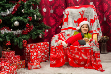 Happy boy with Santa hat sitting in chair
