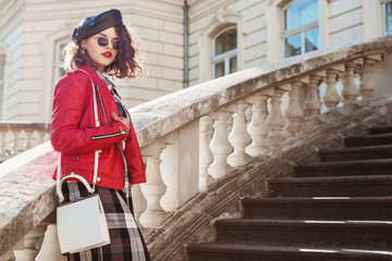 Outdoor fashion portrait of young beautiful fashionable girl wearing autumn checkered dress, red leather biker jacket, beret, sunglasses, carrying white bag, posing in european city. Copy, empty space