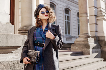 Outdoor fashion portrait of young beautiful fashionable girl wearing blue checkered dress, grey coat, leather beret, sunglasses, holding small bag, posing in european city. Copy, empty space Wall mural