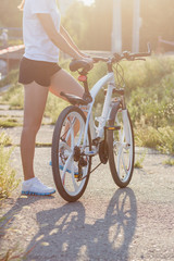 Young sporty woman with a bike, soft focus background