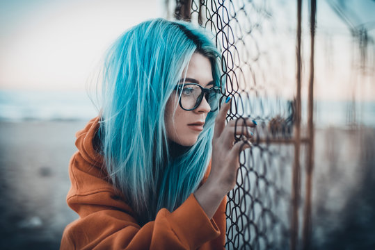 Portrait of young hipster woman with blue hair and glasses sitting on beach near mesh fence