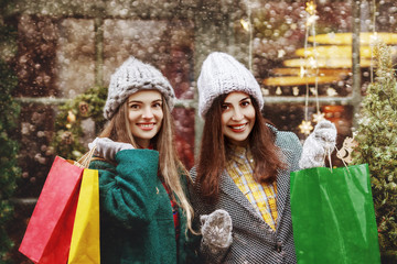 Shopping at Cristmas fair, winter holidays concept: two young beautiful fashionable happy smiling girls posing with colorful paper bags in street. City lifestyle. Ladies wearing stylish coats, hats