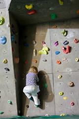 Little kid on climbing wall. Kleins Kind an der Kletterwand.