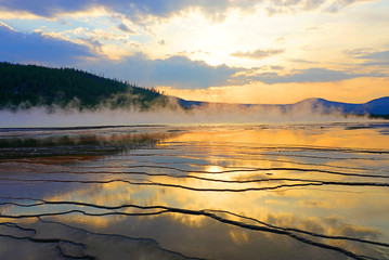 Fiery orange sunset over the Grand Prismatic pool in Yellowstone National Park, United States