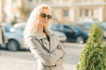 Closeup outdoor portrait of young smiling blond woman with sunglasses with long curly hair. On city street sunny day