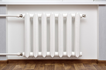 Pipes and a white heating radiator heat the room.