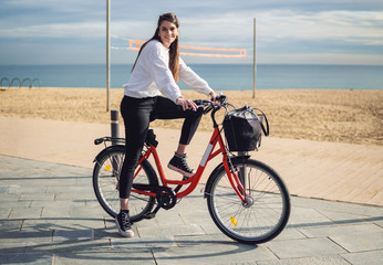 Woman riding bicycle along beach sand at summer time. Healthy and sport concept