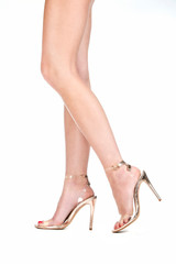 Beautyful legs in high heels in golden color
