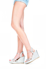 Beautyful legs in silver colored high heels wedges