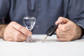 Obraz Męska dłoń trzyma kieliszek z wódką. W drugiej ręce kluczyki od samochodu. - fototapety do salonu