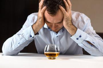 Fototapeta Na kłopoty alkohol. Załamany mężczyzna siedzi przy stole z głową w dłoniach. Szklanka whisky stoi przed nim. obraz