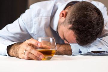 Fototapeta Pijany mężczyzna śpi przy stole z głową opartą o stół. W ręce trzyma szklankę whisky. obraz