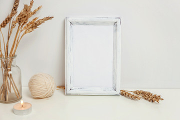 Vertical frame mockup with wild rye bouquet in glass vase near white wall. Empty frame mock up for presentation design. Template framing for modern art. Hygge scandinavian style Natural eco home decor