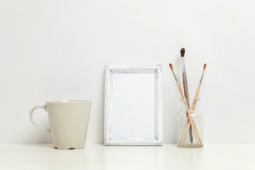 Vertical frame mockup with coffee cup near white wall. Empty frame mock up for presentation design. Template framing for modern art. Hygge scandinavian style workspace. Natural eco home decor
