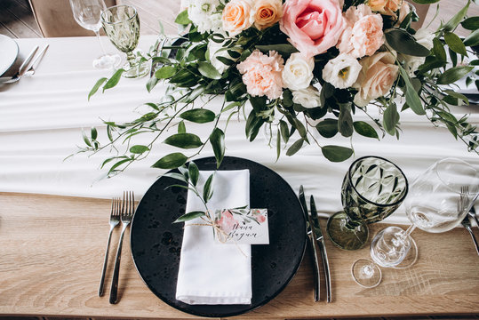 Wedding table serving. Wedding banquet. Beautiful festive table decorated with bouquet of flowers, black plate with card of name guest and cutlery. Top view
