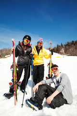 Three friends relaxing at base of ski hill