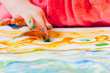 Art, creativity, childhood concept. Little cute child girl painting with fingers.