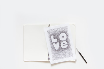 The girl writes the word love in black marker. White sheet. Notebook.