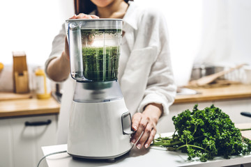 Healthy woman enjoy making green vegetables detox cleanse and green fruit smoothie with blender in kitchen at home.dieting concept.healthy lifestyle