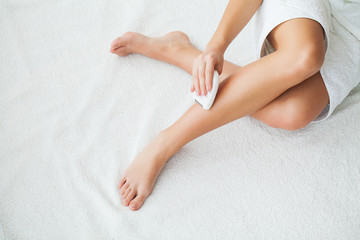 Woman with epilator removing hair on legs