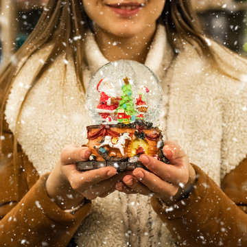 Girl in warm coat holding glass ball with firtrees, house and artificial snow in a mall at the Christmas Fair. Winter mood