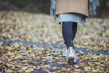 落ち葉の上を歩く女性の足元