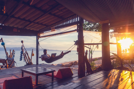 Young attractive guy a man with a beard in a hammock with a laptop on the background of the sea and sunset, distant work, freelancer, blogger, vacation and travel
